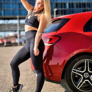Fitgirl standing next to a red Mercedes