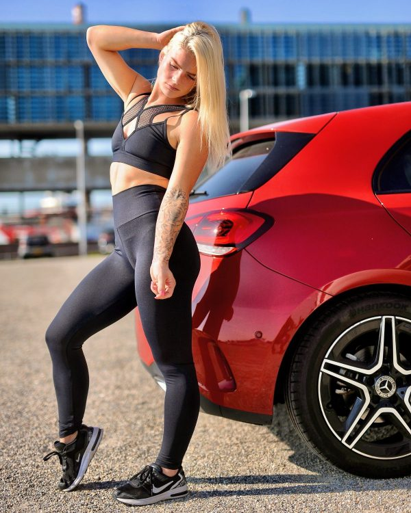 Fitgirl standing next to a red car wearing a infrared legging
