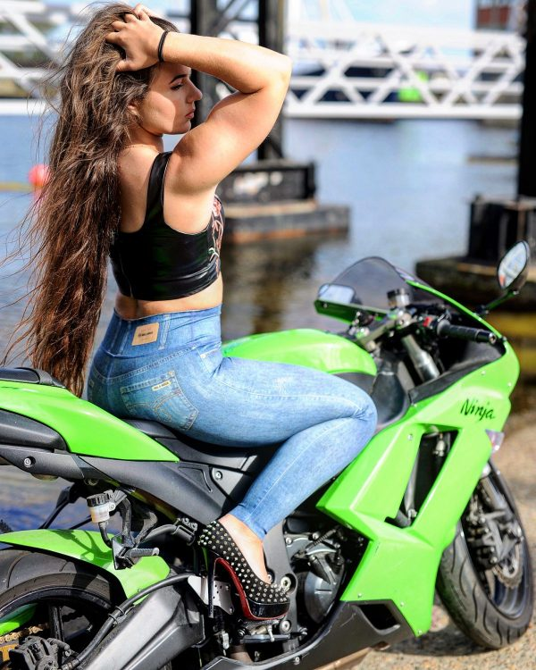 Brunette Fitgirl wearing Rolamoca leggings sitting on her Kawasaki Ninja bike