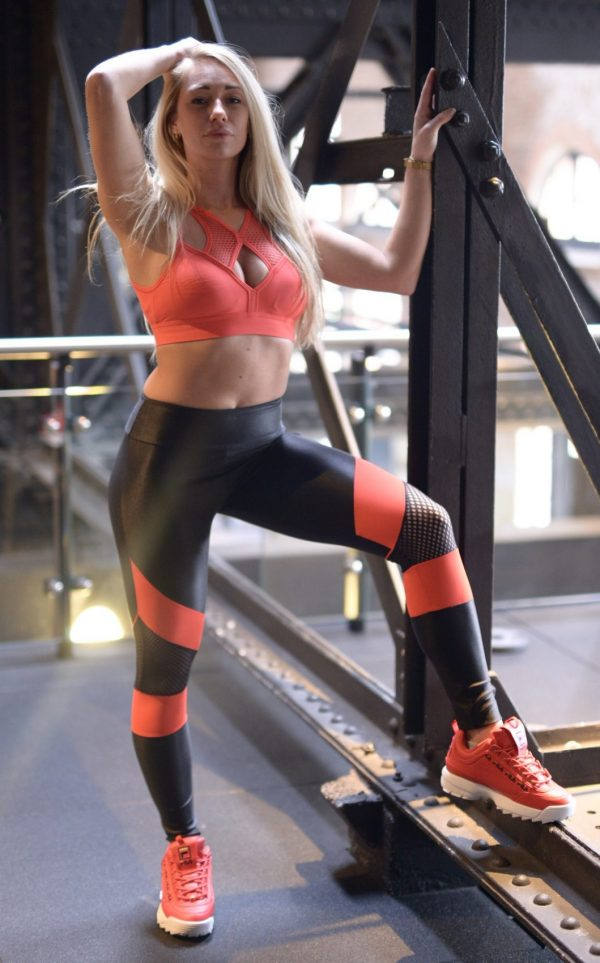 Fitgirl wearing Rolamoca black legging red stripe standing in the gym
