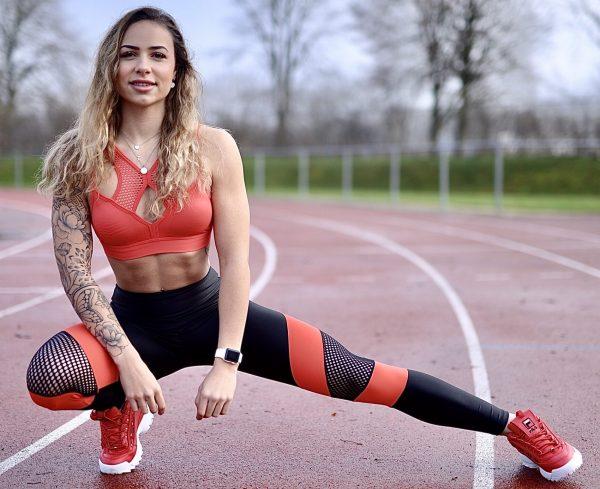 Fitgirl wearing Rolamoca sportswear on a racetrack