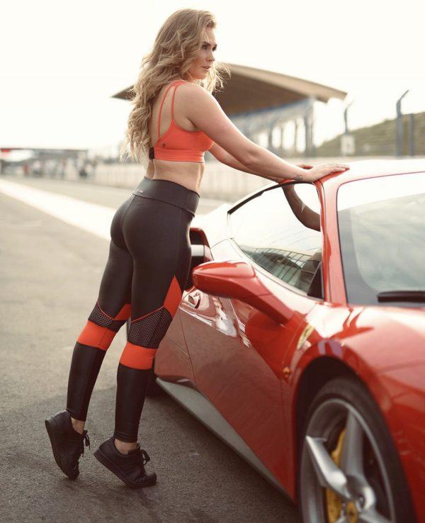 Fitgirl wearing Rolamoca sportswear Standing next to a red sportscar