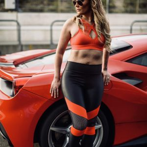 Fitgirl wearing Rolamoca sportswear standing next to a red sportscar