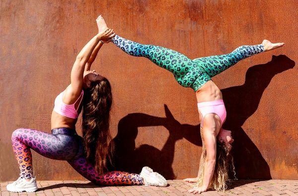 Two fitgirls doing a complicated yoga pose