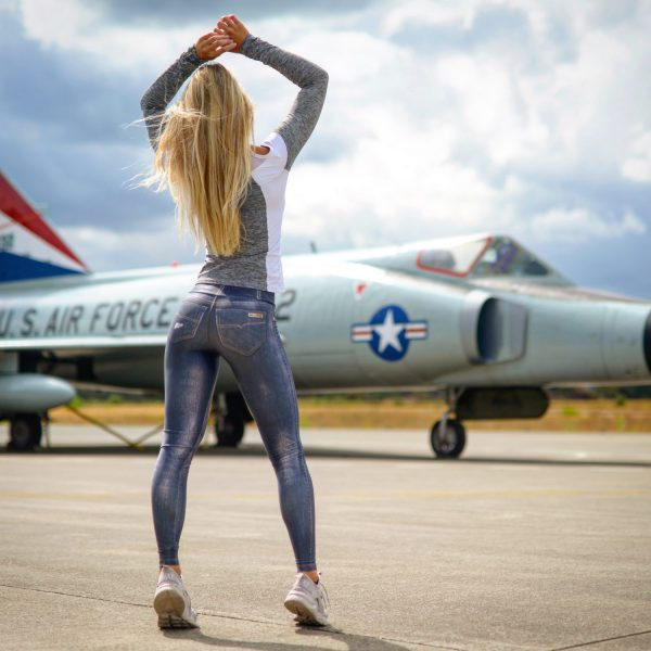 Fitgirl facing a fighter jet wearing jeans leggings