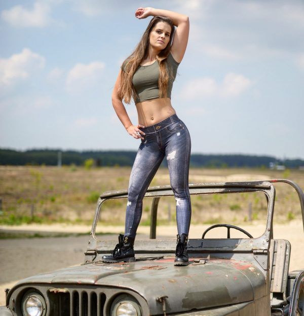 Fitgirl standing on the hood of a jeep wearing a Jeans legging