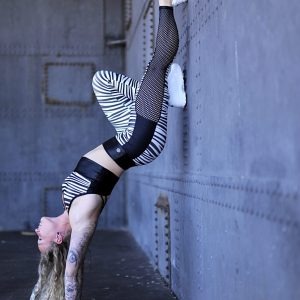 Fitgirl doing a handstand against a wall wearing Rolamoca zebra legging