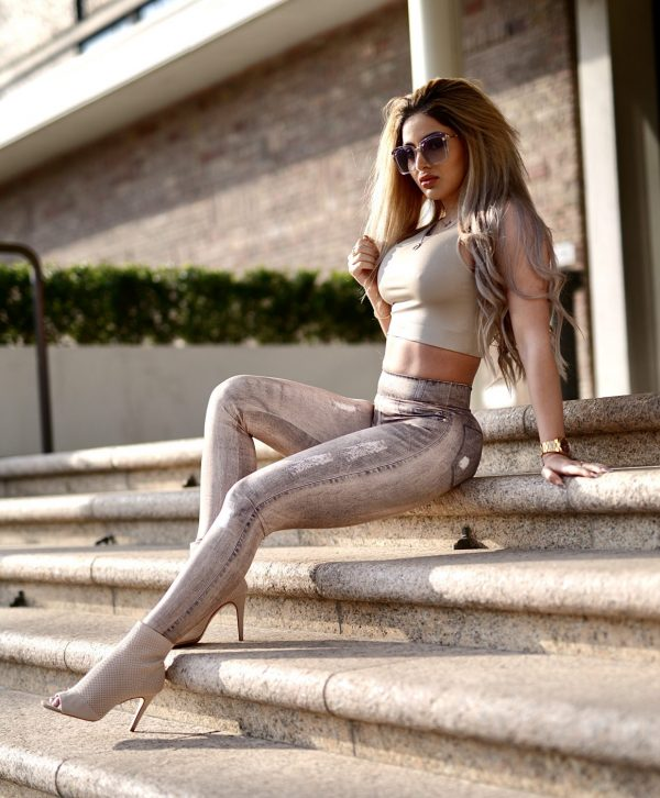 Fitgirl sitting on stairs wearing a Rolamoca Gold Jeans