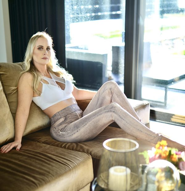Fitgirl wearing Rolamoca gold jeans sitting on a couch