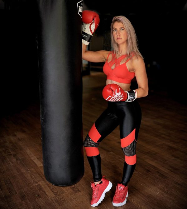 Blonde fitgirl wearing Rolamoca sportswear standing next to a boxing bag