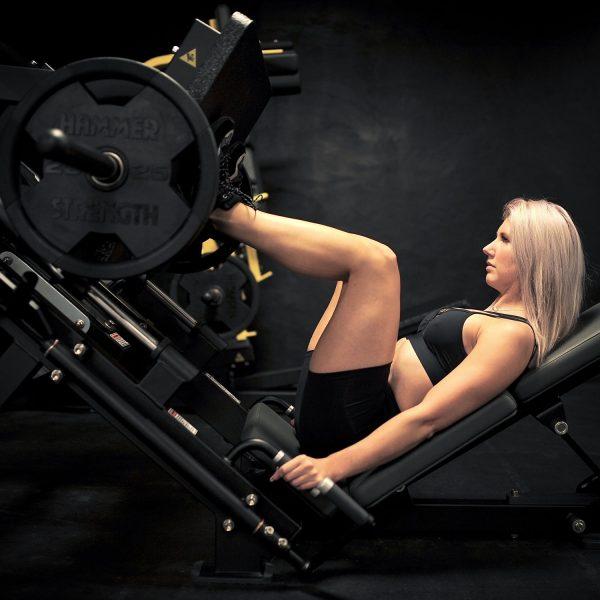 Blonde fitgirl wearing black Rolamoca shorts and sportsbra Doing a legpress