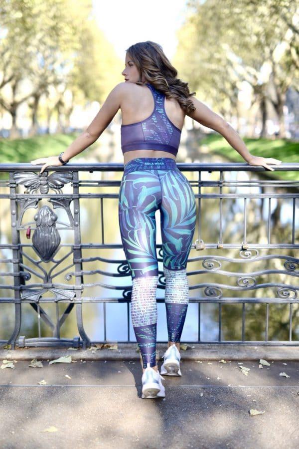 Fitgirl wearing Rolamoca Sportswear leaning against bridge